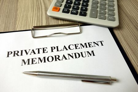 Private placement memorandum with pen and calculator, financial concept