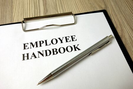 Employee handbook with pen on desk, business concept