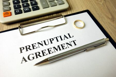 Prenuptial agreement with pen calculator and wedding ring, legal concept