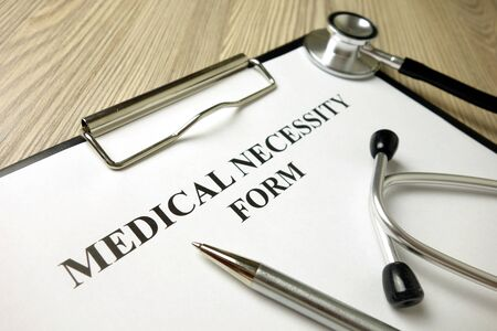 Medical necessity form with pen and stethoscope, healthcare concept