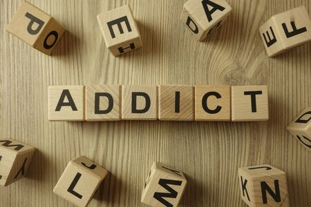 Word addict from wooden blocks, addiction concept Standard-Bild