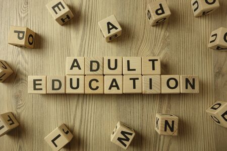 Text adult education from wooden blocks on desk