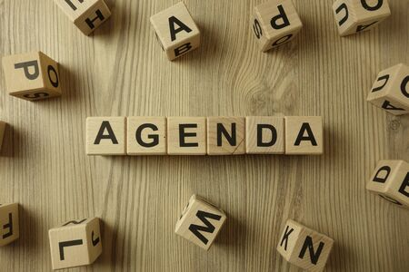 Word agenda from wooden blocks on desk