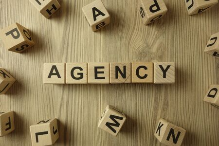Word agency from wooden blocks on desk