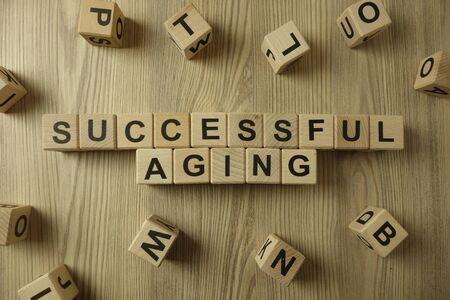 Text successful aging from wooden blocks on desk Standard-Bild