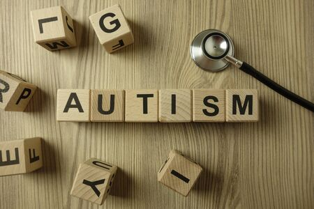 Word autism from wooden blocks with stethoscope, medical concept
