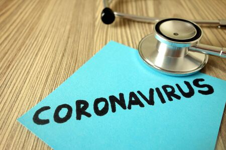 Text coronavirus on sticky note with stethoscope, healthcare and medical concept