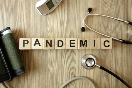Word pandemic with medical accessories on wooden background, healthcare and medicine concept Standard-Bild