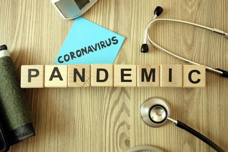 Text coronavirus pandemic with medical accessories on wooden background, healthcare concept Standard-Bild
