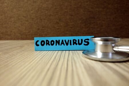 Word coronavirus on sticky note with stethoscope, healthcare and medical concept Standard-Bild