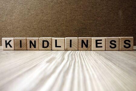 Word kindliness from wooden blocks, friendliness and goodness concept
