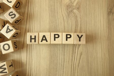 Word happy from wooden blocks on desk Standard-Bild