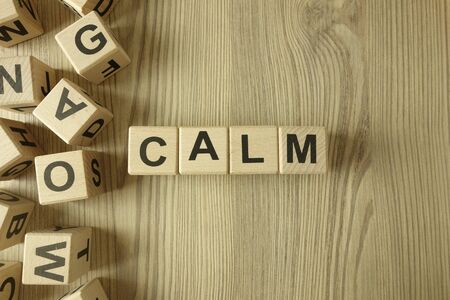 Word calm from wooden blocks on desk