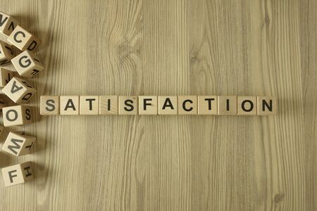 Word satisfaction from wooden blocks on desk
