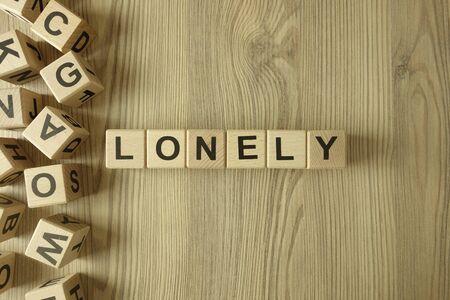 Word lonely from wooden blocks on desk Standard-Bild
