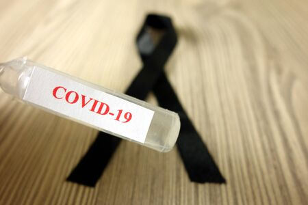 Ampoule with text Covid-19 and black mourning ribbon. Coronavirus epidemic death victim concept Standard-Bild - 143383491