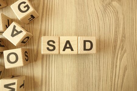 Word sad from wooden blocks on desk Standard-Bild - 144898841