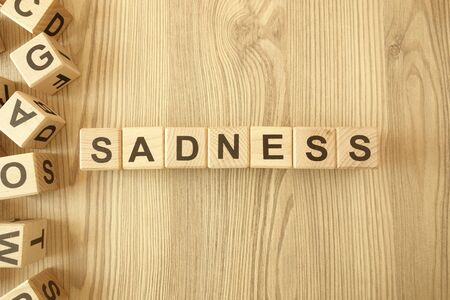 Word sadness from wooden blocks on desk Standard-Bild - 144898842