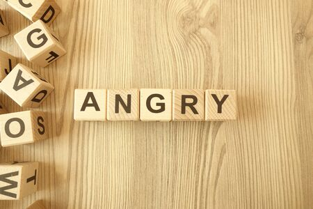 Word angry from wooden blocks on desk