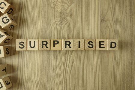 Word surprised from wooden blocks on desk Standard-Bild - 144898848