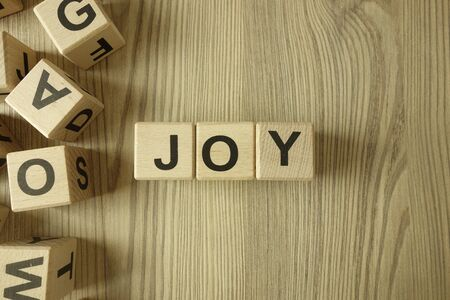 Word joy from wooden blocks on desk Standard-Bild - 144898849