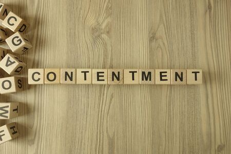 Word contentment from wooden blocks on desk Standard-Bild - 144898748