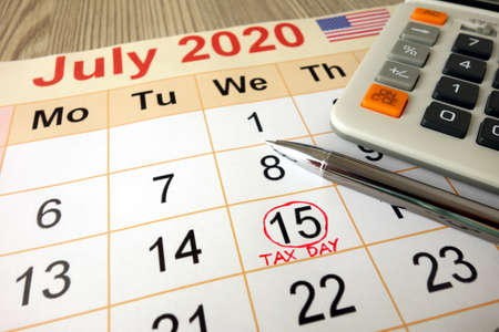 Monthly calendar showing date July 15th 2020 marked as tax day with calculator and pen