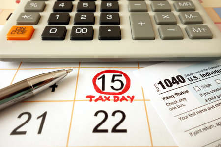 Monthly calendar showing date July 15th 2020 marked as tax day with 1040 form calculator and pen Standard-Bild