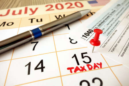 Monthly calendar showing date July 15th 2020 marked as tax day with 1040 form and pen Standard-Bild