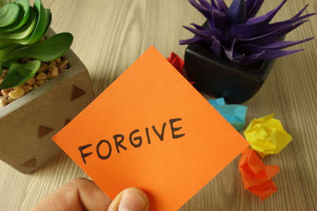 Word forgive handwritten on sticky note, forgiveness concept