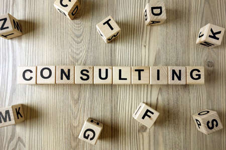 Word consulting from wooden blocks, business concept