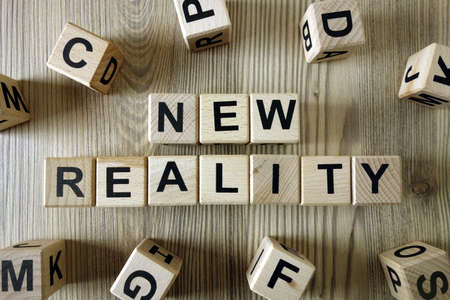 Text new reality from wooden blocks on desk