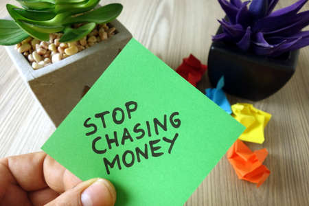 Text stop chasing money handwritten on sticky note, inspirational motivating quote
