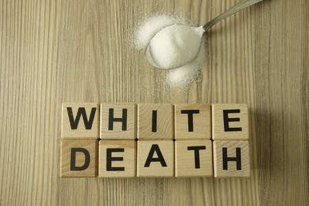 Text white death from wooden blocks with spoon of salt or sugar, healthcare concept