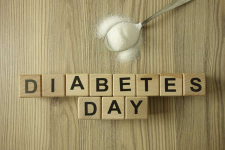 Text diabetes day from wooden blocks with spoon of sugar, healthcare concept