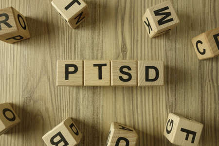 Word PTSD post traumatic stress disorder from wooden blocks, depression and trauma concept