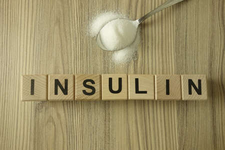 Word insulin from wooden blocks with spoon of sugar, healthcare concept 免版税图像