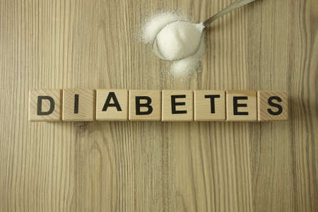Word diabetes from wooden blocks with spoon of sugar, medical concept