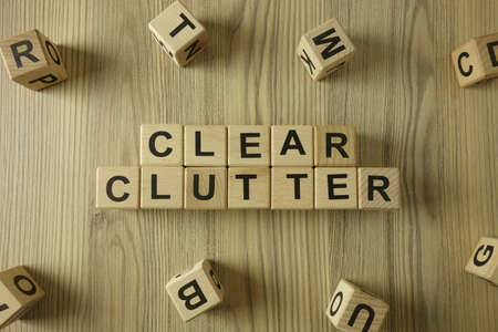 Text clear clutter from wooden blocks, positive thinking and motivation concept