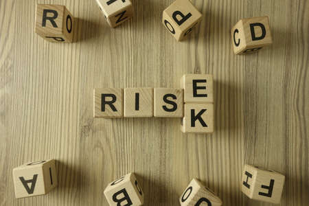 Word rise or risk from wooden blocks, business strategy and assessment concept
