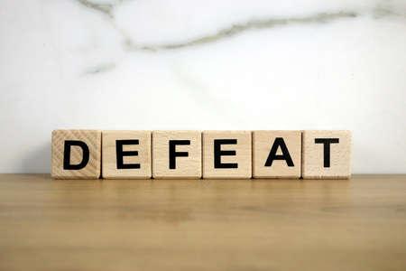 Word defeat from wooden blocks on desk 免版税图像