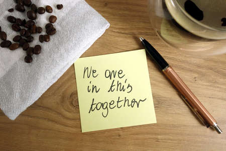 We are in this together note handwritten on sticky note with coffee and pen, help and support during pandemic concept 免版税图像