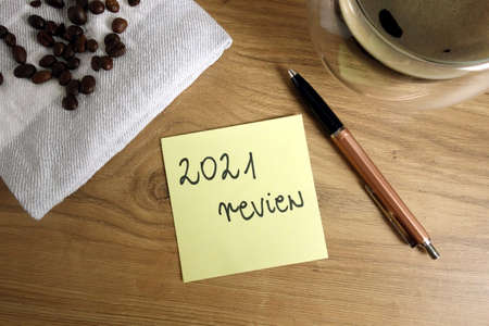 Text 2021 review handwritten on sticky note, year summary concept 免版税图像