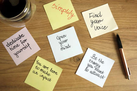 Inspirational and motivational slogans handwritten on sticky notes with pen and coffee, self development concept