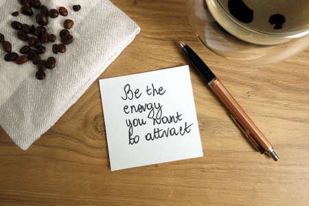 Be the energy you want to attract text handwritten on sticky note with coffee and pen, law of attraction concept 免版税图像