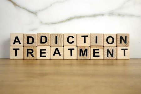Addiction treatment text from wooden blocks, addict rehabilitation concept