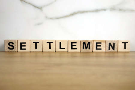 Settlement word from wooden blocks, business or law deal concept 免版税图像