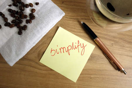 Word simplify handwritten on sticky note, clarify business concept