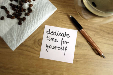 Slogan dedicate time for yourself handwritten on sticky note, self care concept