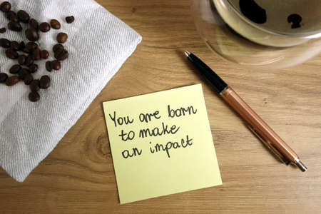 You are born to make an impact text handwritten on sticky note with coffee and pen, positive attitude concept